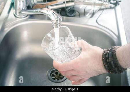 Homme tenant UN verre au-dessus de l'évier de cuisine le remplir Avec l'eau qui coule du robinet