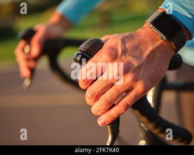 Gros plan des mains sur le guidon. Cycliste professionnel avec montre intelligente en plein air au coucher du soleil