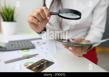 La main féminine tient la loupe et l'argent à la table de travail