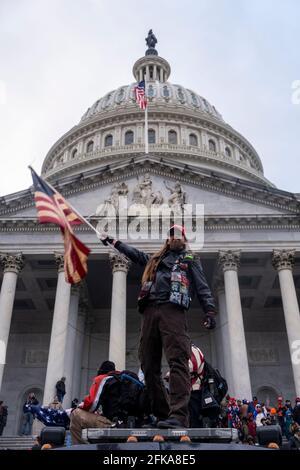 Washington DC, États-Unis. 6 janvier 2021. Un homme fait un drapeau devant le Capitole lors de la tempête du bâtiment par les partisans de Trump.