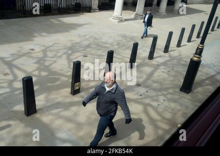 Deux hommes étrangers qui se strident marchent alors qu'ils sont séparés par des bollards de sécurité sur Whitehall à Westminster, le centre du gouvernement britannique, le 27 avril 2021, à Londres, en Angleterre.