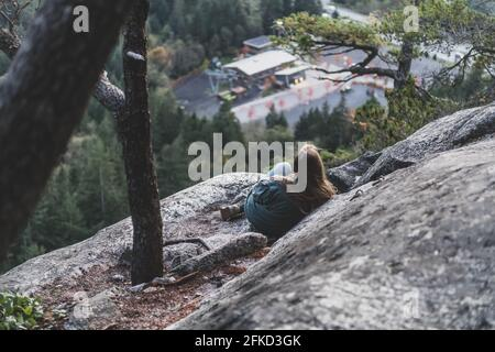 Canada, Colombie-Britannique, Squamish, jeune femme assise sur le rocher
