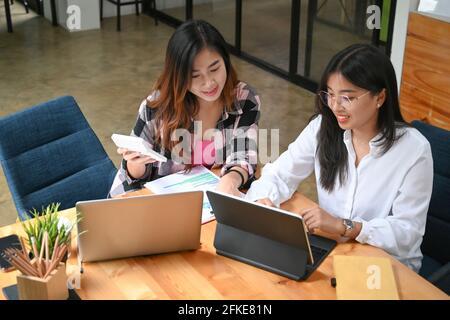 Deux jeunes créateurs asiatiques travaillent ensemble dans un espace de travail commun.