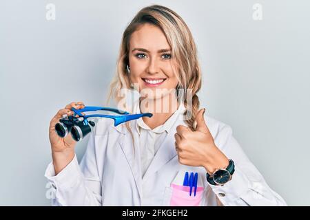 Belle jeune femme blonde tenant des lunettes scientifiques souriant heureux et positif, pouce vers le haut faisant excellent et signe d'approbation