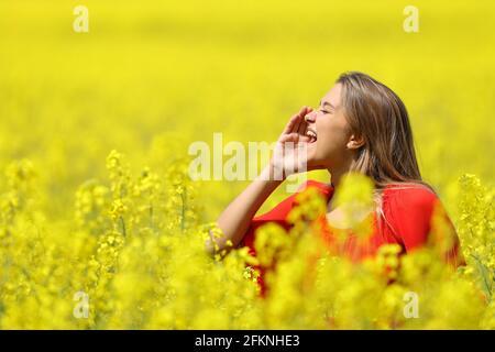 Bonne femme criant avec la main sur la bouche dans un jaune champ au printemps