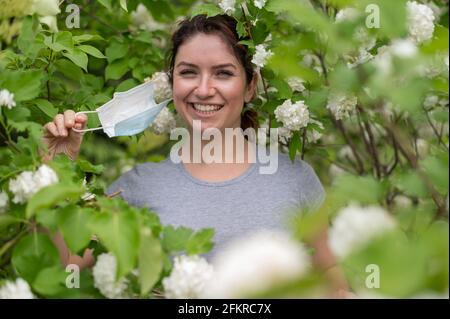 Une femme heureuse aux cheveux rouges prend un masque médical tout en se tenant à côté d'un pommier en fleur dans un parc. Fin de la rhinite allergique saisonnière. La fille