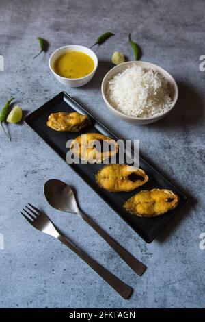 Menu du déjeuner de style bengali, poisson frit servi avec du riz vapeur et des légumes secs.