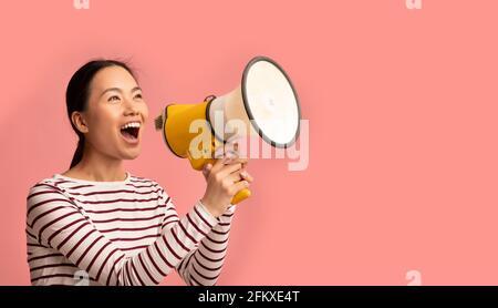 Annonce. La jeune femme asiatique avec le mégaphone entre les mains criant à Copy Space