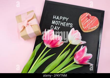 Carton noir avec lettres en plastique blanc avec citation Happy Mothers Day, sur fond rose. Vue de dessus