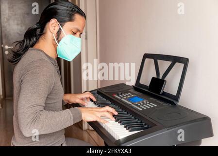 Jeune latino-américain apprenant à jouer du piano à la maison pendant quarantaine