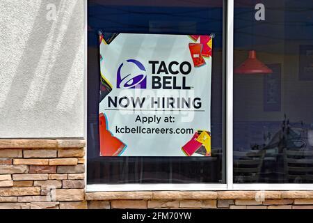 Emporia, Kansas, États-Unis. 6 mai 2021. Taco Bell embauche maintenant des affiches affichées dans la fenêtre de Taco Bell local à Emporia, Kansas, alors que les entreprises cherchent à embaucher des employés et à augmenter la production normale après la pandémie de COVID-19 le 6 mai 2021. Crédit : Mark Reinstein/Media Punch/Alamy Live News