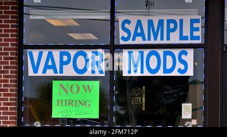 Emporia, Kansas, États-Unis. 6 mai 2021. Des affiches d'embauche sont maintenant affichées à la fenêtre de l'atelier local de fumée Vapor à Emporia, Kansas, alors que les entreprises cherchent à embaucher des employés et à augmenter la production normale après la pandémie de COVID-19, le 6 mai 2021. Crédit : Mark Reinstein/Media Punch/Alamy Live News