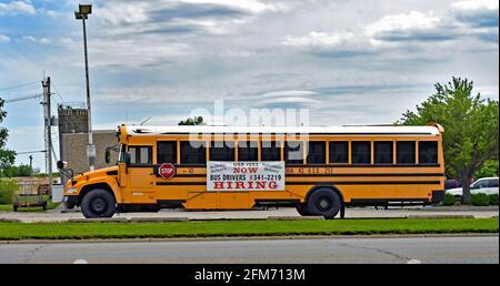 Emporia, Kansas, États-Unis. 6 mai 2021. Les conducteurs d'autobus scolaires ont besoin de panneaux d'embauche sont affichés sur le côté de l'autobus scolaire à Emporia, Kansas, alors que les entreprises cherchent à embaucher des employés et à augmenter la production normale après la pandémie COVID-19 le 6 mai 2021. Crédit : Mark Reinstein/Media Punch/Alamy Live News