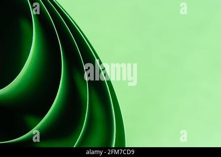 Arrière-plan de macro de couleur abstraite, créé avec des feuilles de papier vertes incurvées. Lignes et formes incurvées et couleurs vives et douces.