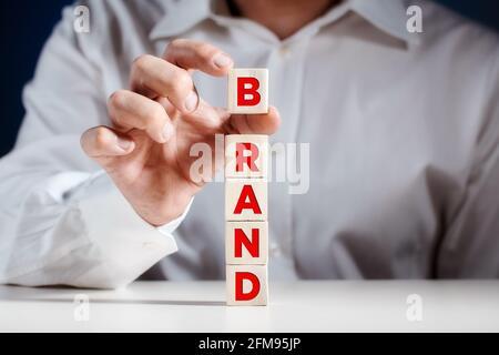 Homme d'affaires met un cube sur des cubes de bois à plusieurs niveaux avec le mot marque. Concept d'entreprise marketing de création de marque.