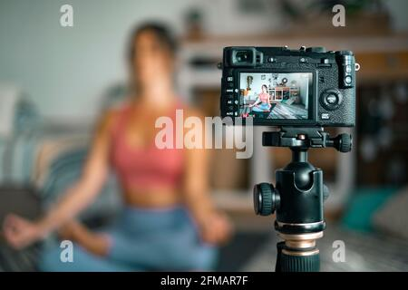 Jeune femme s'exerçant à la maison faisant pilates et l'enregistrement à elle dispose d'un appareil photo numérique pour enseigner l'entraînement et produire du web classe - créateur de contenu affaires libre sain style de vie personnes concept