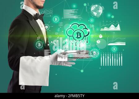 Beau jeune serveur en tuxedo tenant des icônes de devise sur le plateau