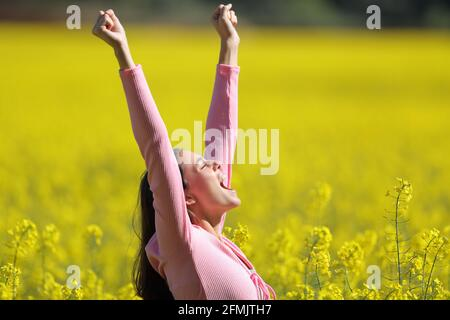 Vue latérale d'une femme excitée qui soulève les bras un champ jaune au printemps
