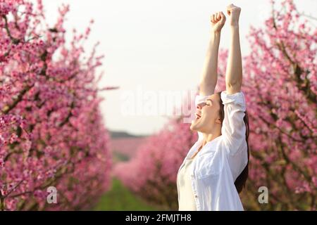 Une femme excitée se levant les bras célébrant le printemps dans un rose fleuri champ