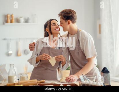 Le couple heureux aimant prépare la pâtisserie dans la cuisine.