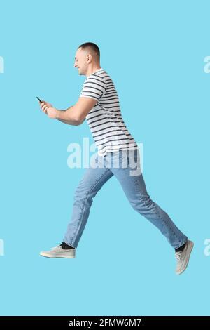 Sautant un jeune homme avec un téléphone portable sur fond de couleur