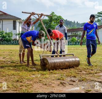 Galle, Sri Lanka - 04 17 2021: Joueurs et personnel préparant le terrain et le terrain de cricket après une forte pluie. Enlever l'excès d'eau et de boue pendant que roller u