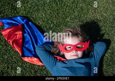 Portrait d'un enfant portant un costume de super-héros posé sur l'herbe. Super héros enfant s'amuser dans le parc à l'extérieur. Concept de puissance pour enfants.