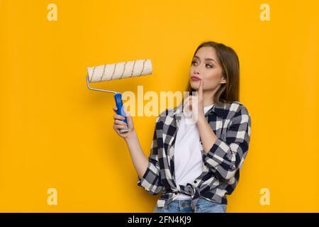 Jeune femme blonde en chemise de bûcherons tient le rouleau de peinture et de penser. Taille relevée sur fond jaune
