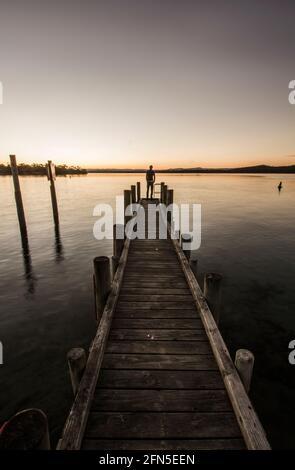 Photographie de style de vie éloigné d'une silhouette masculine debout au bout d'une jetée d'océan en regardant un magnifique paysage marin au coucher du soleil. Fins et débuts