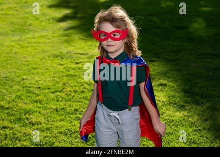Super-héros enfant s'amuser en plein air. Super héros garçon sur la nature. Garçon portant un costume de super-héros et s'amusant à l'extérieur.