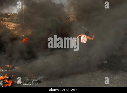 Des manifestants palestiniens sont vus à côté de pneus en feu lors d'une protestation contre les tensions à Jérusalem et l'escalade Israël-Gaza, près de Ramallah, en Cisjordanie occupée par Israël, le 16 mai 2021. REUTERS/Ammar Awad