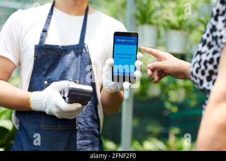 Travailleur de serre en gants de protection tenant le temps et acceptant sans contact Paiement du client à l'aide de la technologie NFC