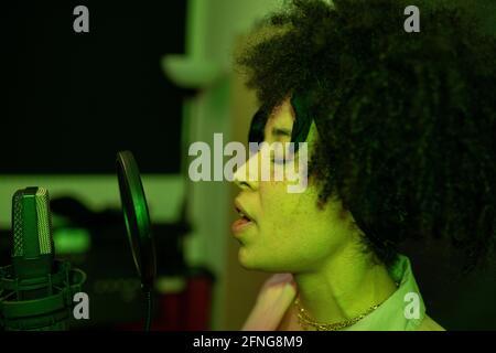 Une chanteuse noire interprète une chanson contre un microphone avec filtre pop en vous tenant debout et en gardant les yeux fermés dans un studio de son
