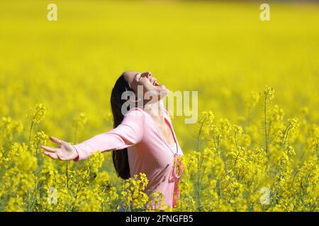 Profil d'une femme excitée criant s'étendant des bras dans champ à fleurs jaunes