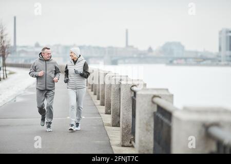 Couple senior actif positif en combinaisons de sport grises en train de courir ensemble le long de la rivière en hiver et de parler entre eux