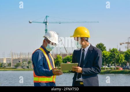 Deux personnes un ingénieur travaille en équipe en extérieur sur la construction du site
