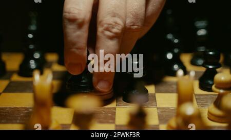 La personne utilise le pion sur le plateau dans le jeu d'échecs.