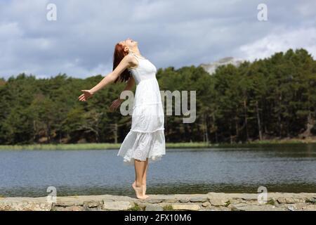Profil complet d'une femme de beauté qui s'étire les bras célébrant vacances avec une robe blanche dans un lac