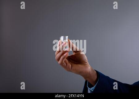 Gros plan d'un homme d'affaires tenant la base à vis de l'ampoule contre le gris arrière-plan