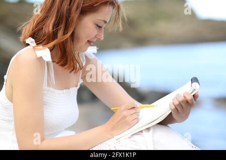 Bonne femme en robe blanche dessin sur le carnet sur le plage