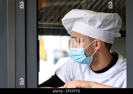 Un jeune chef portant un masque Covid pendant une pause de travail. Milan, Italie - mai 2021