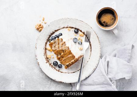 Tranche de gâteau de carottes avec noix et glaçage au fromage à la crème servi avec des myrtilles fraîches sur une assiette avec une tasse de café, vue du dessus