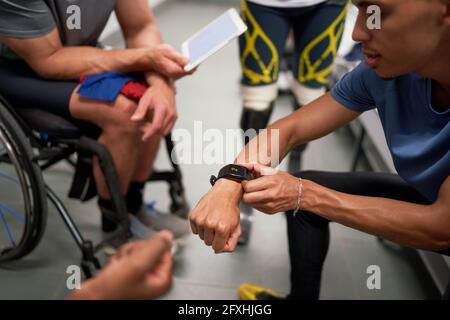 Hommes amputés et athlètes en fauteuil roulant avec téléphone intelligent dans le vestiaire