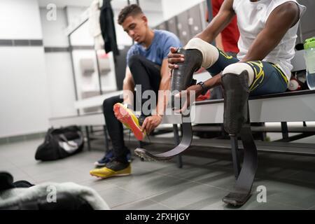 Athlète amputé de sexe masculin qui règle la prothèse de la lame de course dans le vestiaire