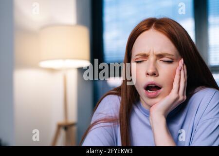 Portrait d'une jeune femme fatiguée travaillant à taper sur un ordinateur portable au bureau à domicile, se sentant surtravaillée et épuisée.