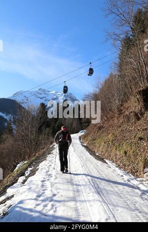 un seul homme randonnée sur un sentier enneigé sous les téléphériques
