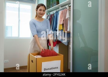 Une femme asiatique se tient près d'un placard de vêtements dans le dressing et porte une boîte de vêtements donnés à apporter au centre de dons.