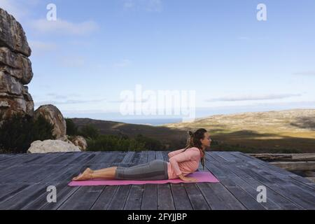 Bonne femme caucasienne pratiquant le yoga allongé sur le pont s'étirant cadre rural de montagne