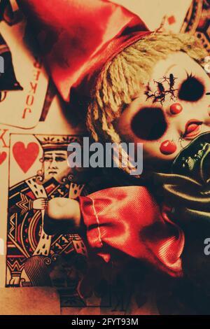 Gros plan du vieux fissurés poupée vêtue comme joker sur jeu de carte avec photo du roi