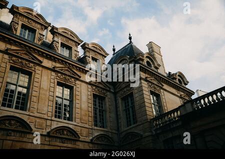 Photo d'un bâtiment marron avec de grandes fenêtres sous les nuages